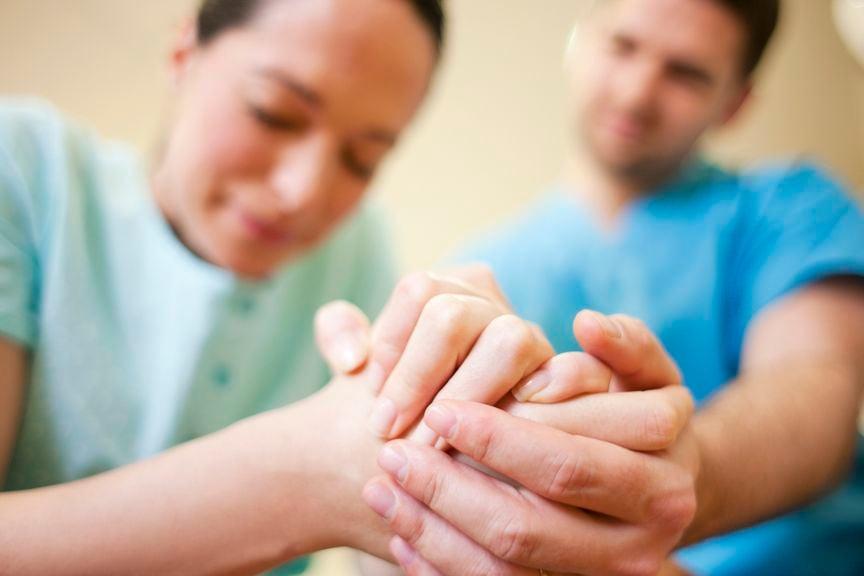 Mann hält die Hand seiner Frau