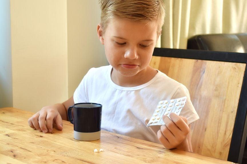 Kind mit Medikamenten in der Hand