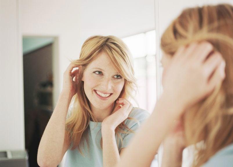 Frau lächelt ihr Spiegelbild an