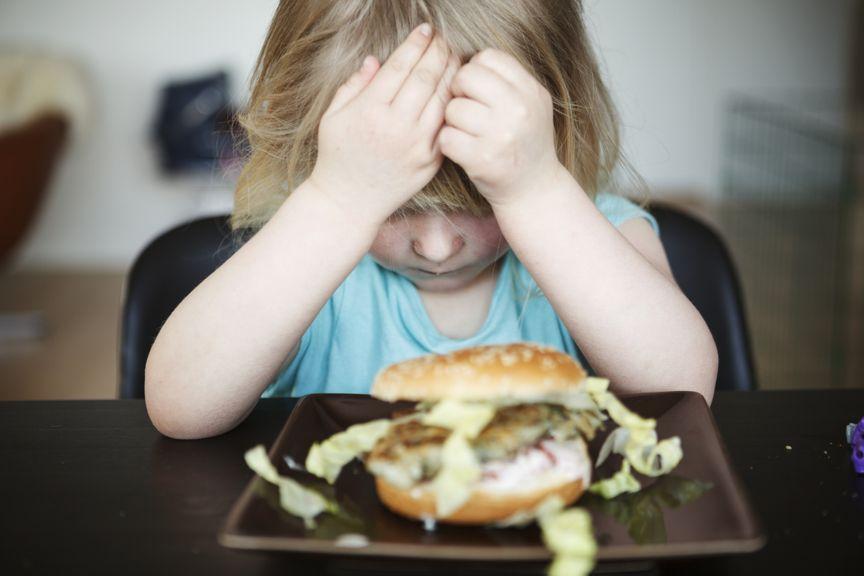 Kind sitzt vor dem Teller, mag nicht essen