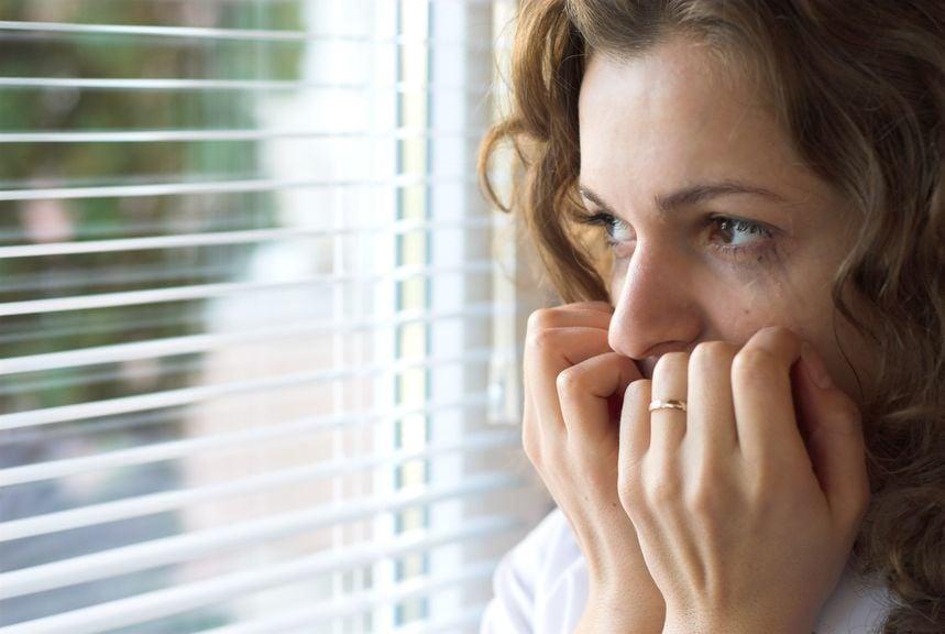 Frau blickt aus dem Fenster, Hände vor dem Mund