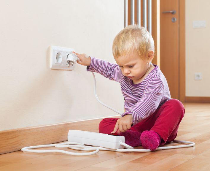 Kind spielt mit Stromkabeln