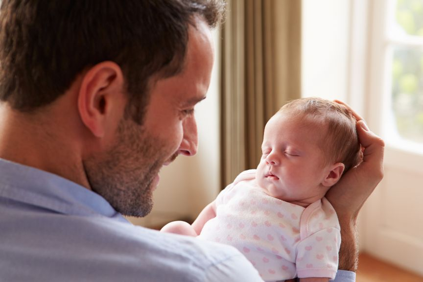 Vater betrachtet liebevoll sein schlafendes Baby