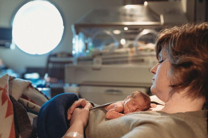 Mutter hält Frühgeborenes auf dem Bauch