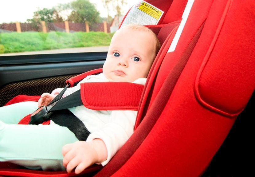 Baby im Autositz angegurtet