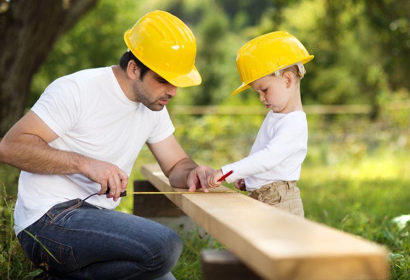 Vater und Sohn mit Schutzhelmen bei der Arbeit mit Holz