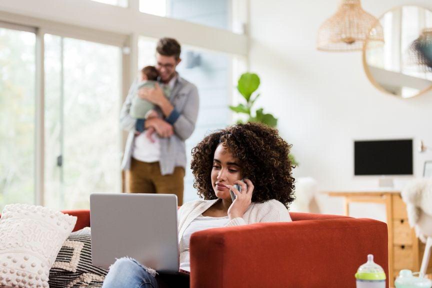 Mutter arbeitet im Home Office, Vater kümmert sich ums Baby