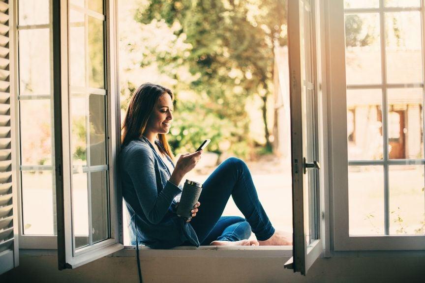 Frau sitzt im Fensterrahmen und schaut in ihr Smartphone