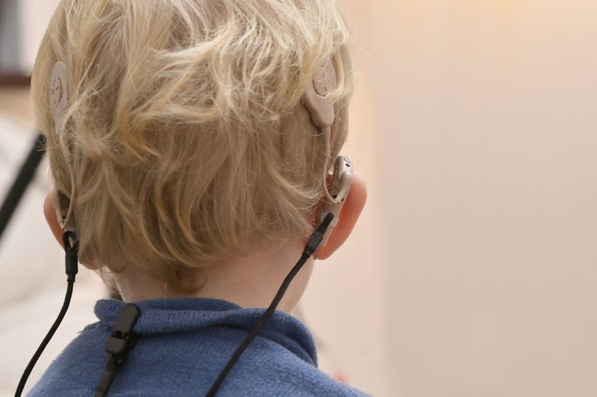 Kind mit Hörgeräten und Cochleaimplantaten