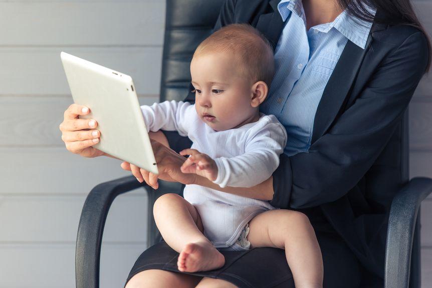 Frau, im Bürostuhl, mit Baby auf dem Schoss und Tablett