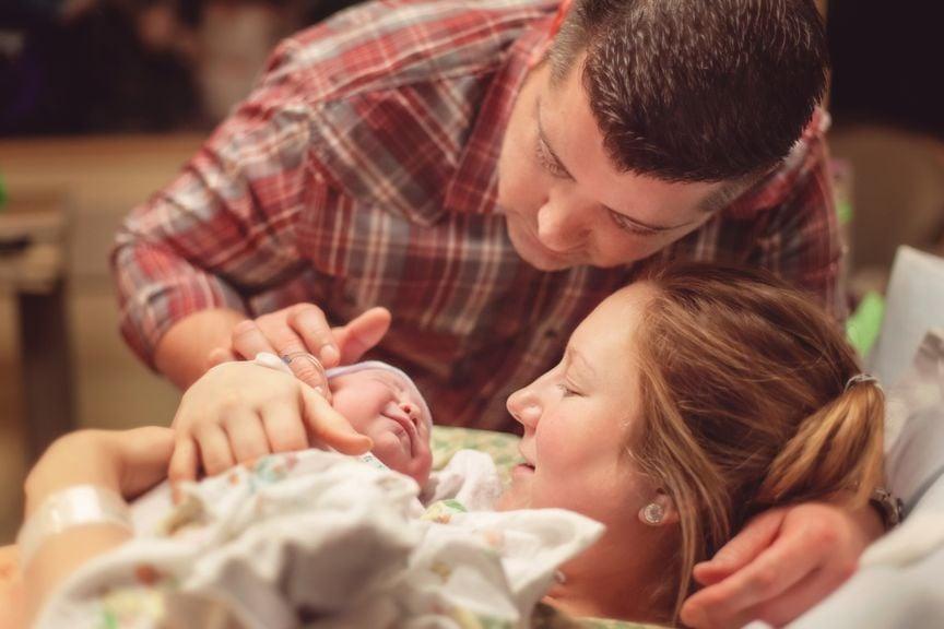 Paar schaut ihr Neugeborenes an