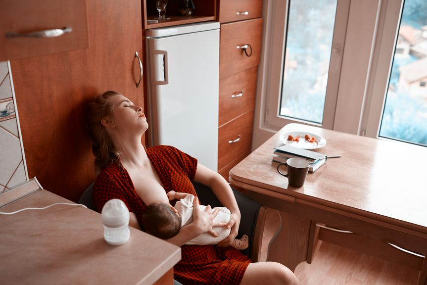 Erschöpfte Mutter beim Stillen