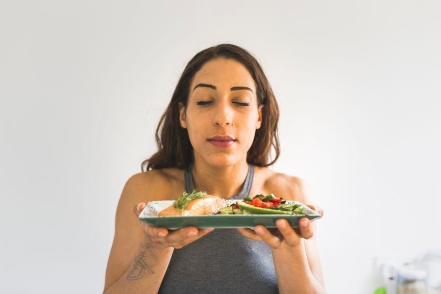 Frau hält einen Teller mit Lachs und Gemüse