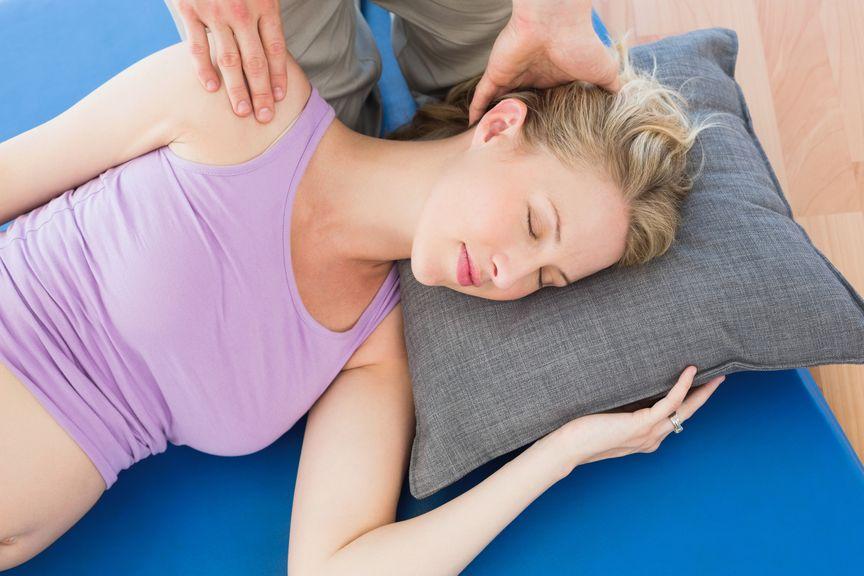 Schwangere wird an Kopf und Schulter behandelt