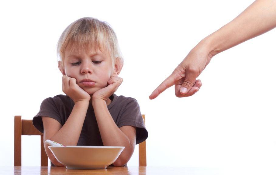 Kind sitzt unwillig vor dem Essen,Kind sitzt vor dem Teller und will nicht essen