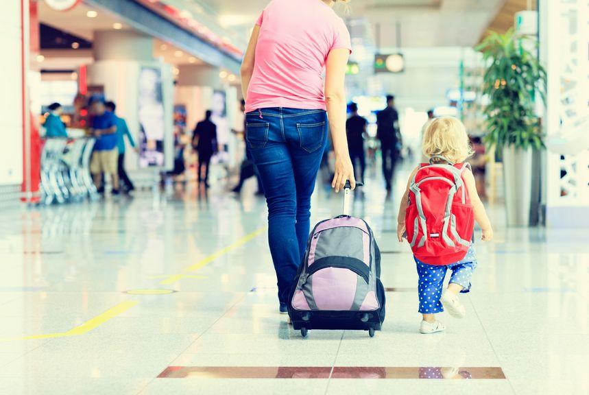 Mutter mit Kind und Gepäck in der Flughafenhalle