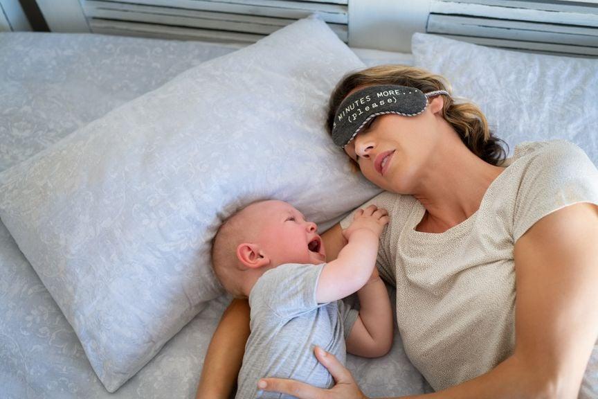 Mutter mit schreiendem Baby im Bett