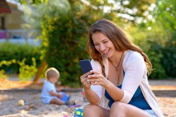 Mutter auf Spielplatz mit Smartphone,Spielplatz Smartphone