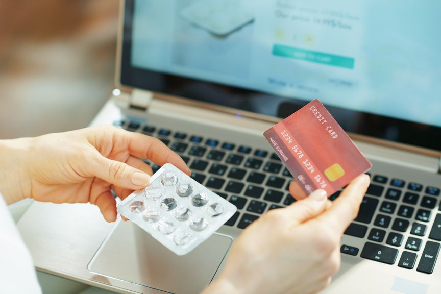 Frau mit leerer Blisterpackung und Kreditkarte vor dem Laptop