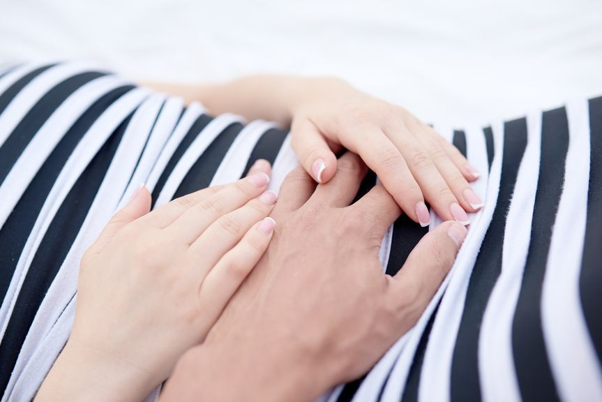 Frau hält die Hand ihres Partners auf dem Bauch