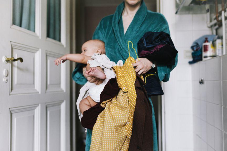 Mutter mit Baby und Kleidern unter dem Arm