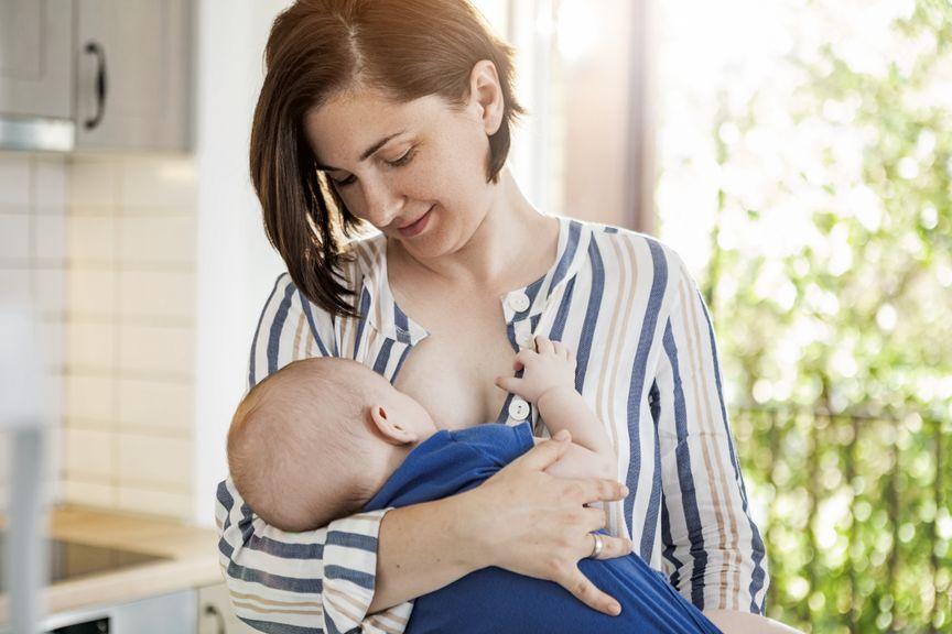 Mutter hält und stillt ihr Baby