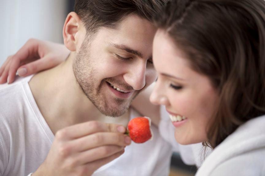 Junger Mann füttert junge Frau mit einer Erdbeere