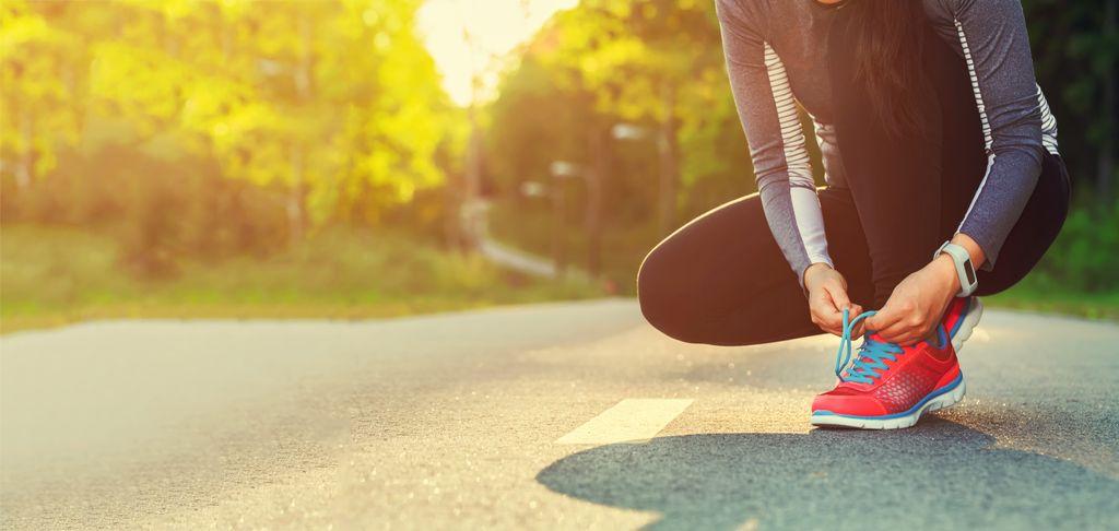 Frau bindet ihre Sportschuhe zum Joggen