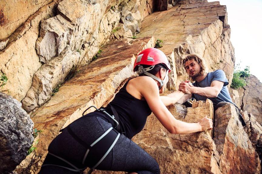 Schwangere beim Klettern an der Felswand, der Partner hilft
