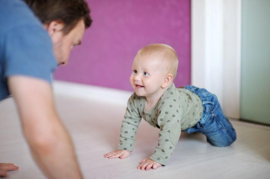 Vater und Baby krabbeln aufeinander zu
