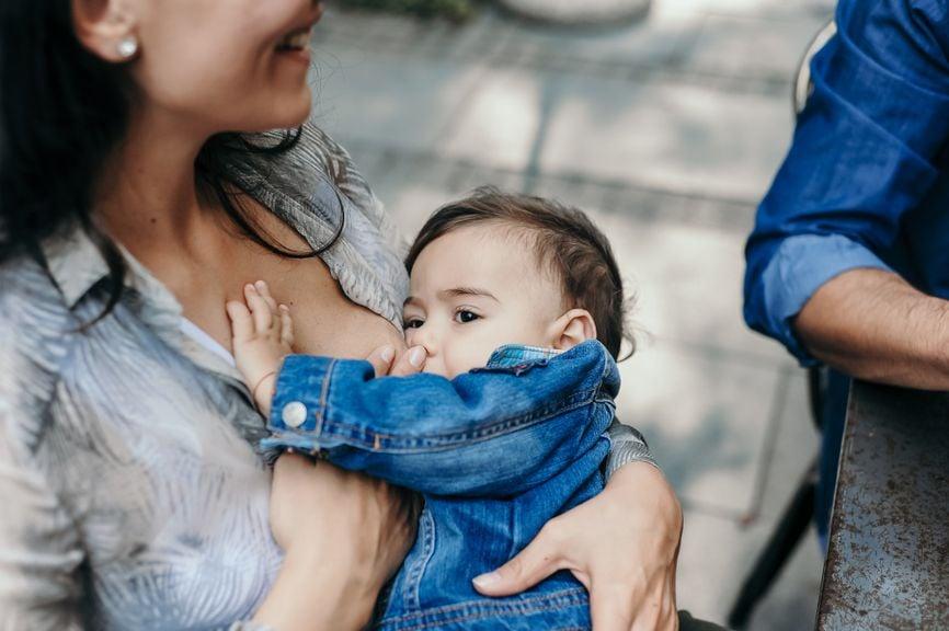 Mutter stillt ihr Kind im Freien