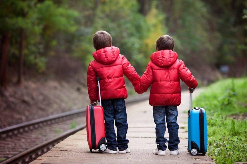 Kinder mit Koffern am Bahngleis