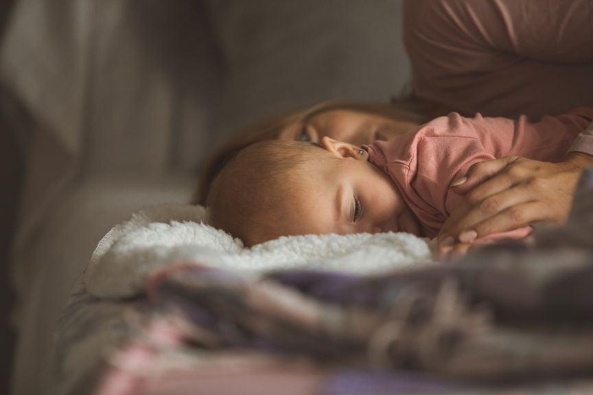 Mutter kuschelt mit Baby im Bett