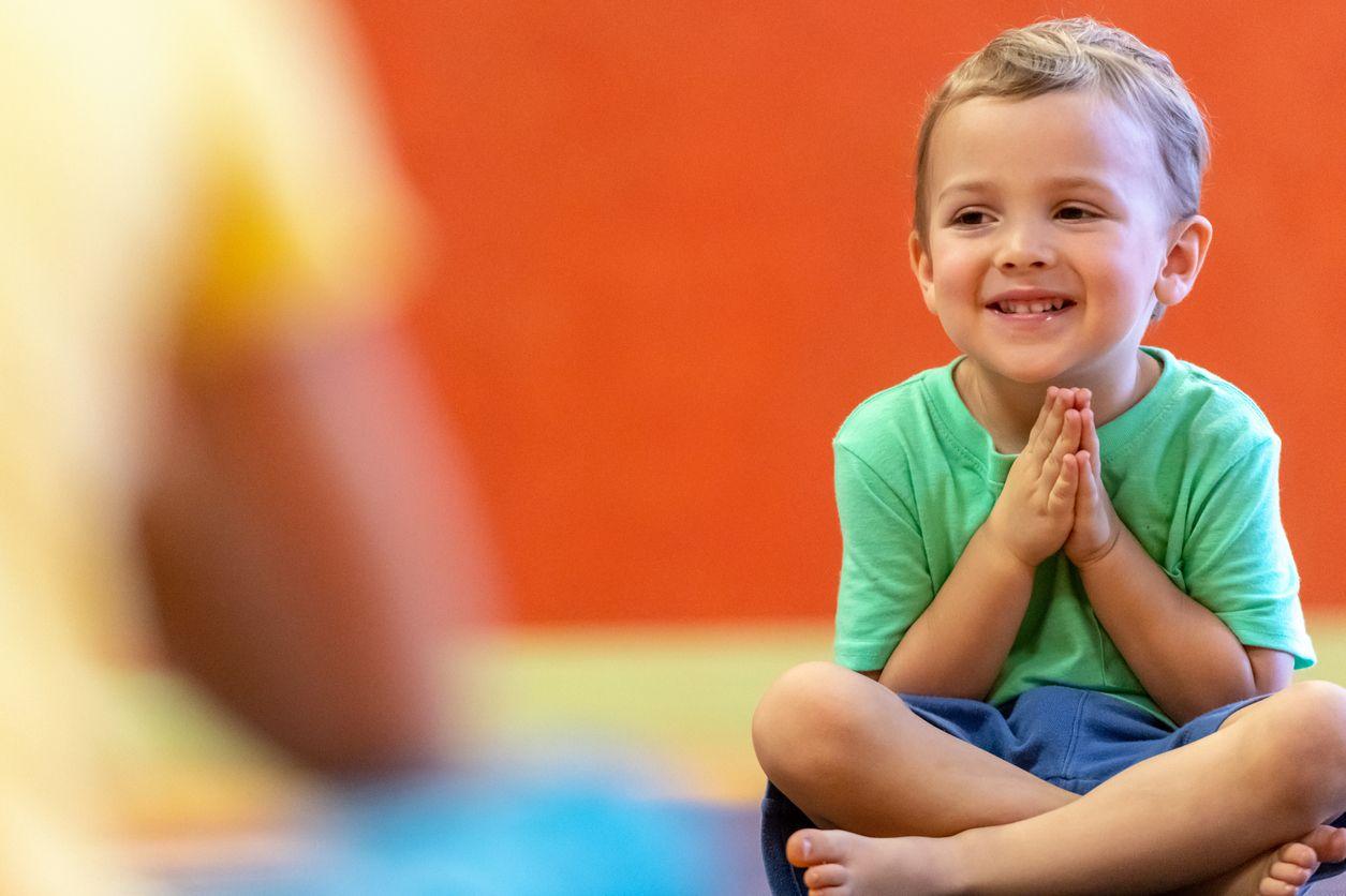 Junge sitzt im Schneidersitz auf dem Boden