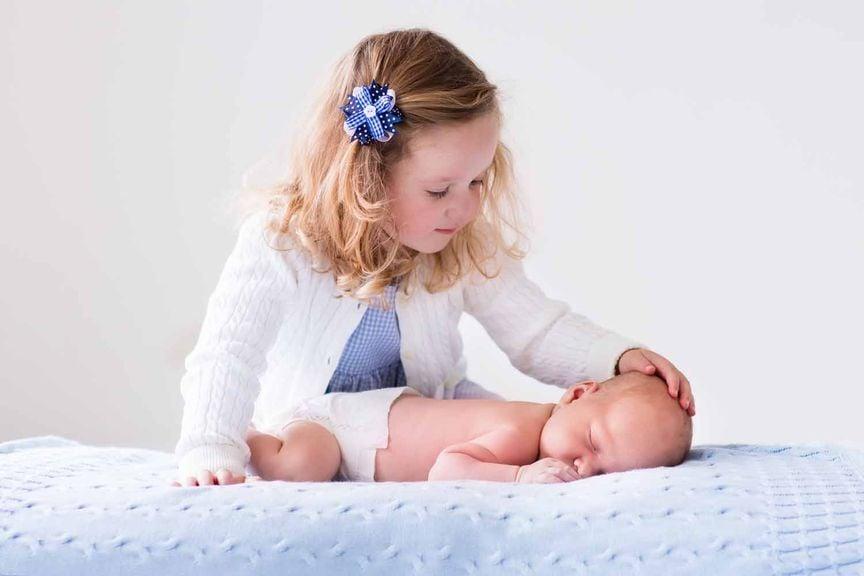 Schwester streichelt ihr neugeborenes Geschwisterchen
