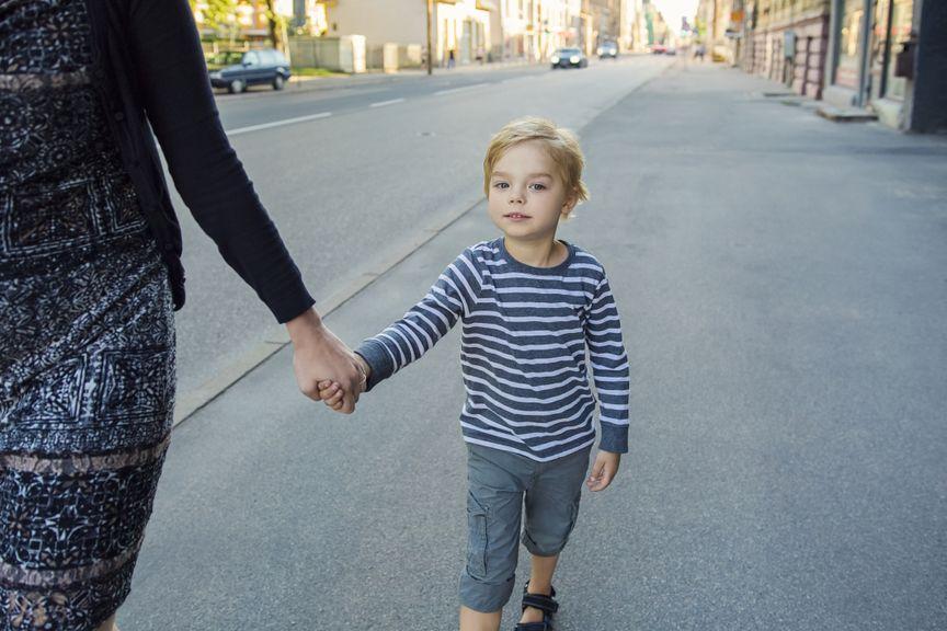 Junge an der Hand der Mutter auf dem Trottoir