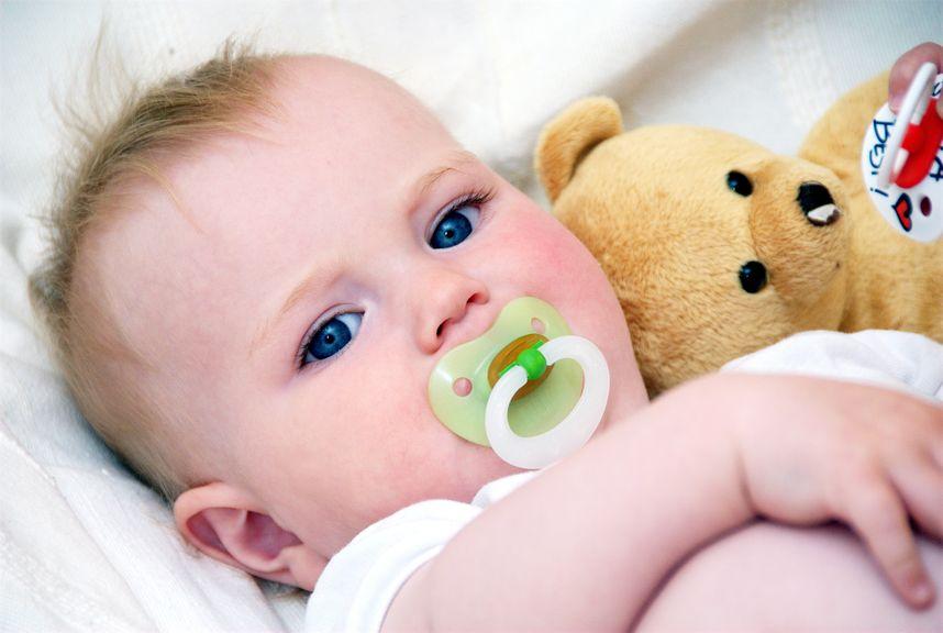 Baby im Bett mit Nuggi und Teddybär