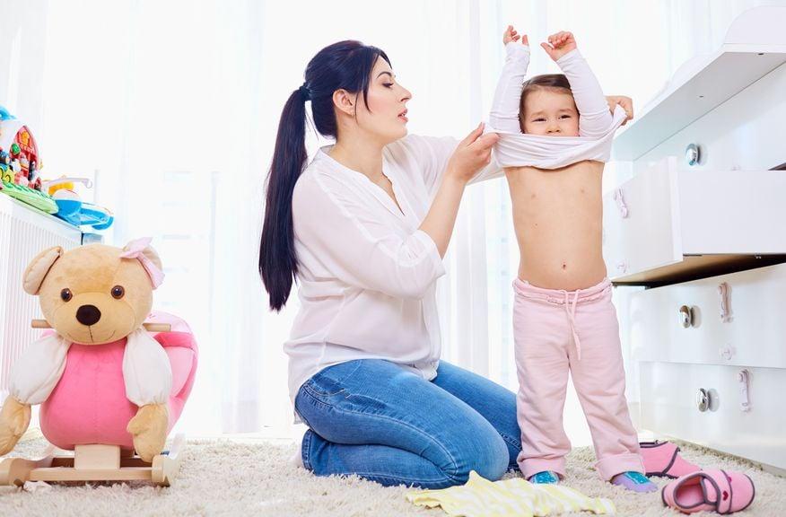Erwachsene hilft Kind sich auszuziehen