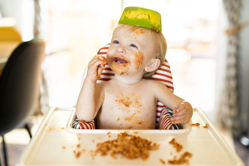 Kind mit Pasta verschmiertem Gesicht und Teller auf dem Kopf