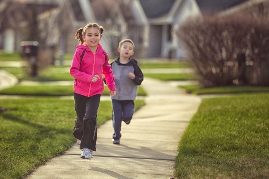 Junge und Mädchen joggen auf dem Trottoir