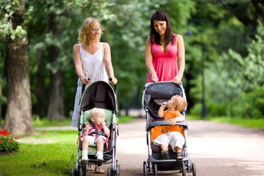 Zwei Mütter gehen mit Kinderwagen spazieren