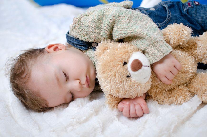 Baby schläft mit Teddy im Arm