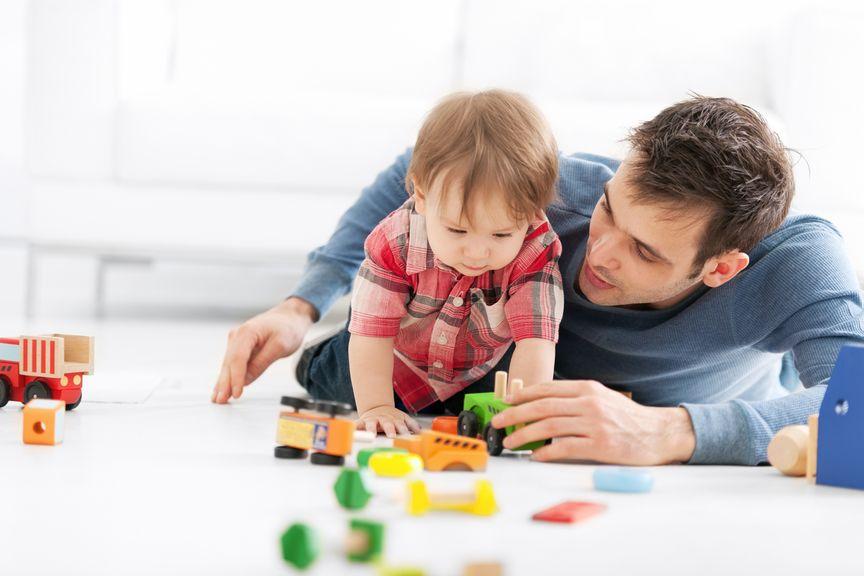 Vater spielt mit seinem Kind mit Holzautos am Boden