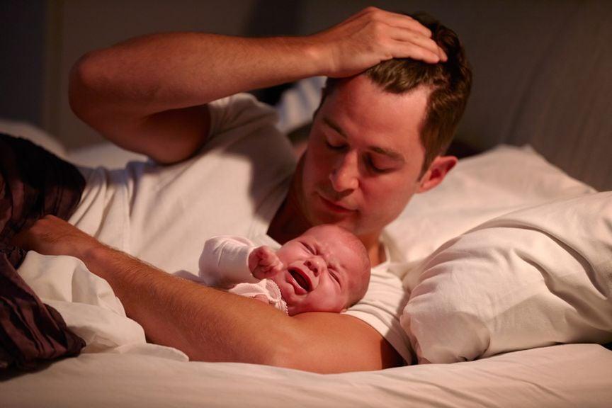 Vater mit schreiendem Baby im Bett