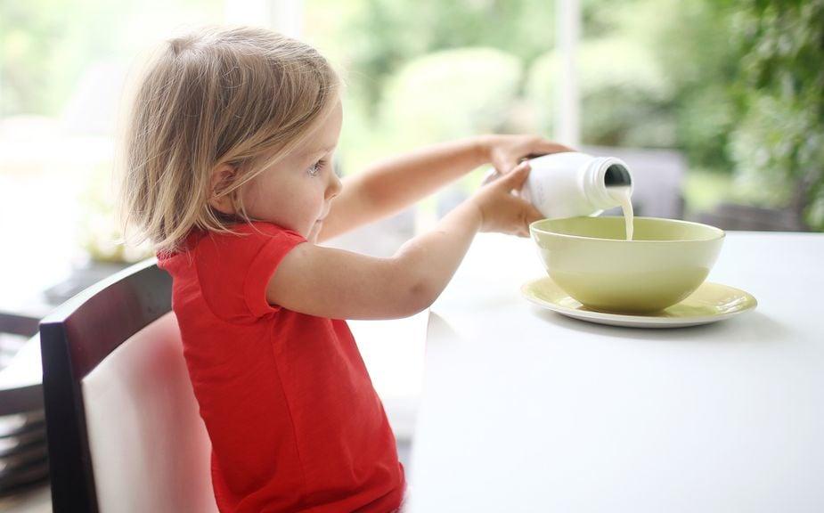 Kind giesst Milch in eine Schale