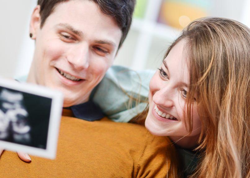 Paar betrachtet erfreut das Ultraschallbild ihres Babys