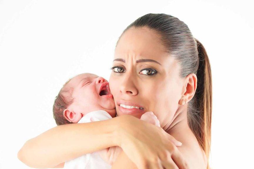 Besorgte Mutter mit schreiendem Säugling im Arm
