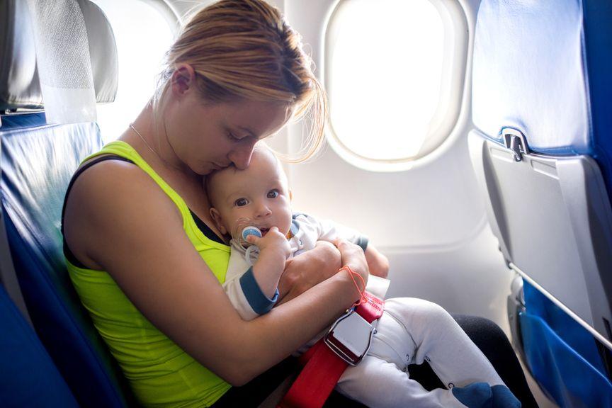 Baby mit Babybelt und Mutter im Flugzeug
