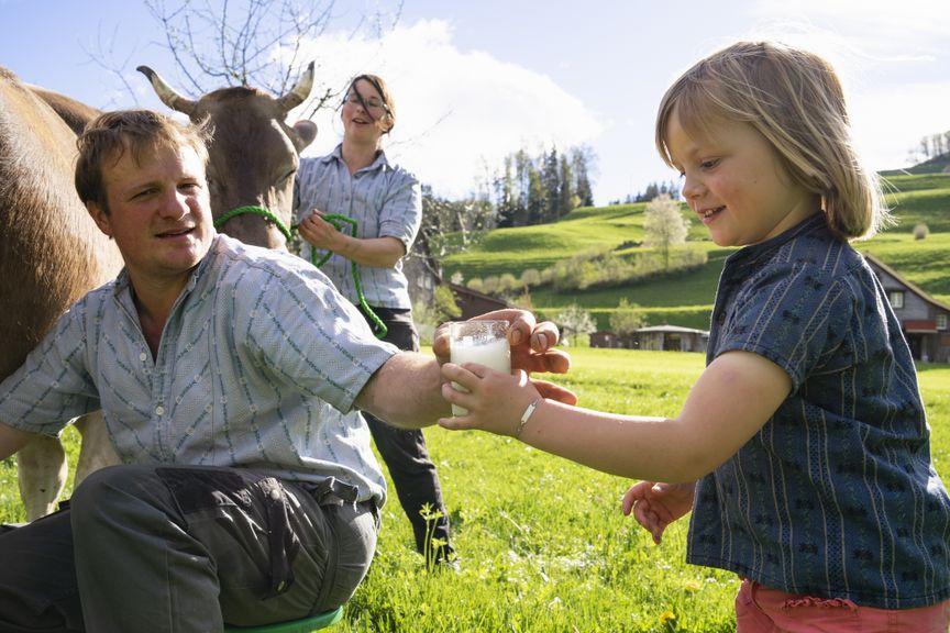 Kind nimmt ein Glas Milch direkt nach dem Melken