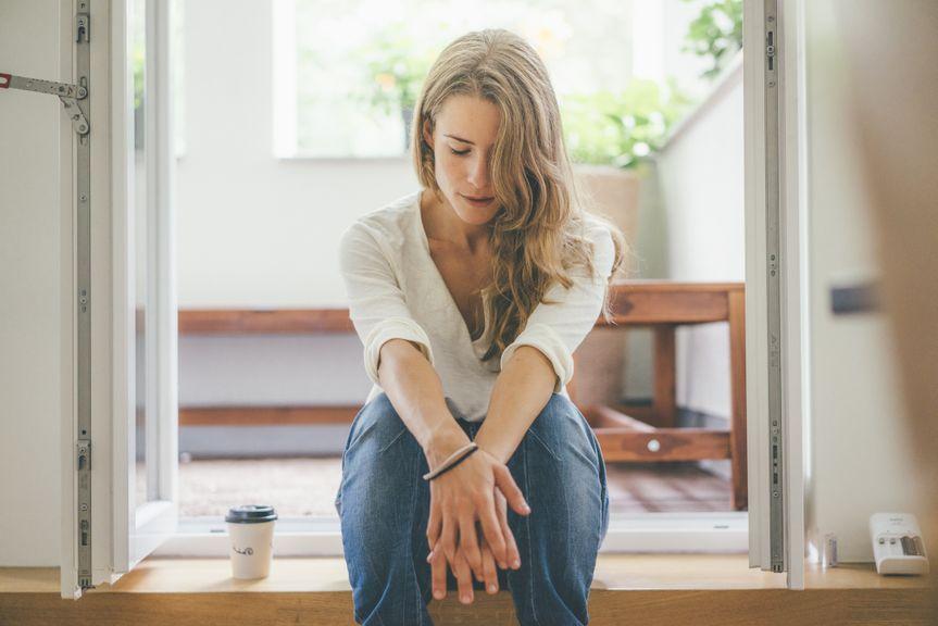 Nachdenkliche Frau sitzt mit Kaffeebecher an der Balkontür